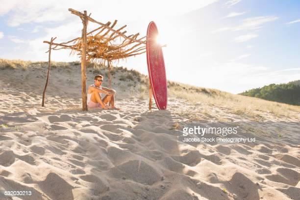 Caucasian man sitting under wooden canopy on beach