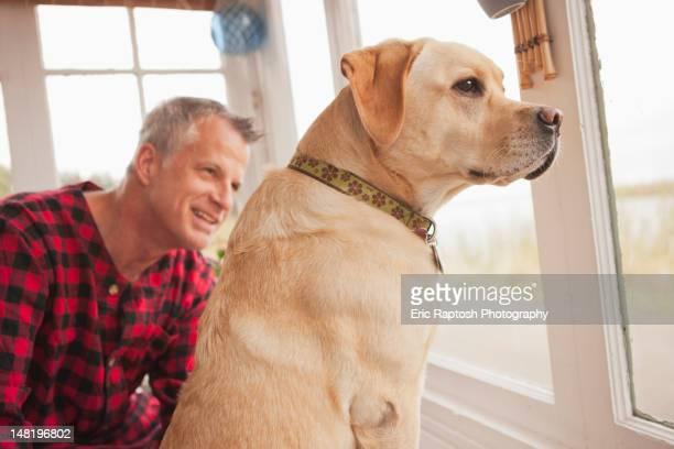 Caucasian man sitting with labrador