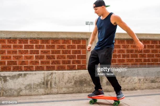 caucasian man skateboarding near brick wall - só homens jovens imagens e fotografias de stock