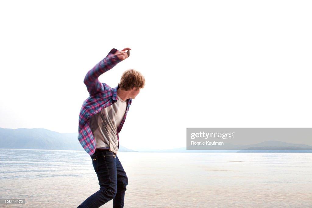 Caucasian man skimming stones on lake : Stock Photo