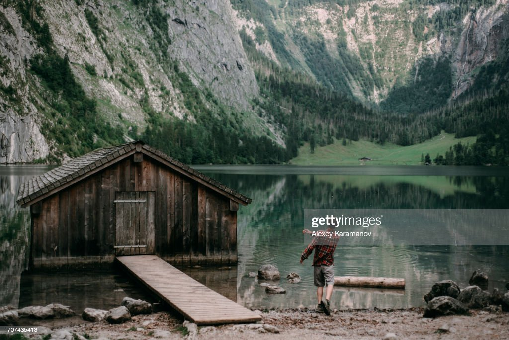 Caucasian man skipping stones in mountain lake : Stock Photo