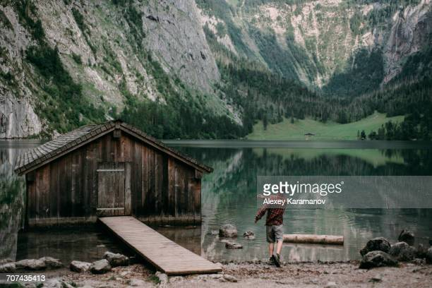 caucasian man skipping stones in mountain lake - skipping along stock pictures, royalty-free photos & images