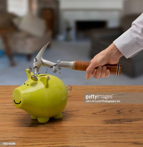 Caucasian man smashing piggy bank