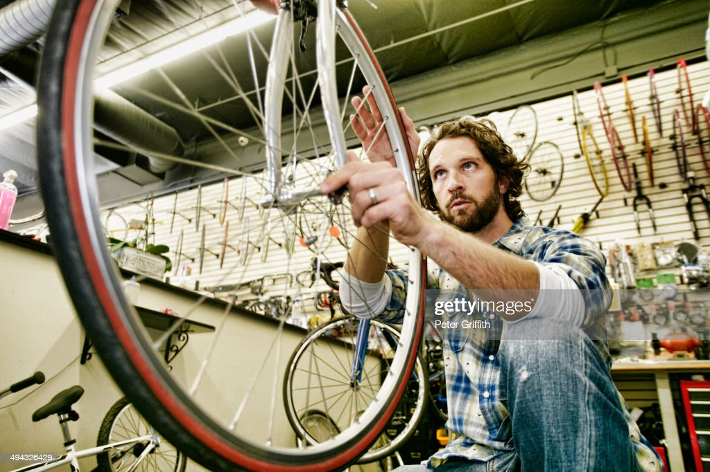 Caucasian man smiling in bicycle repair shop : ストックフォト