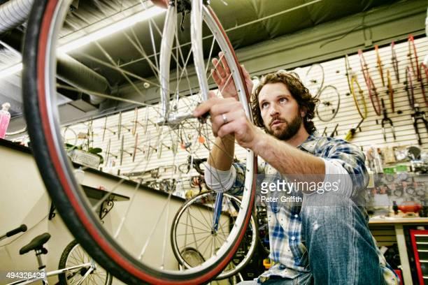 Caucasian man smiling in bicycle repair shop