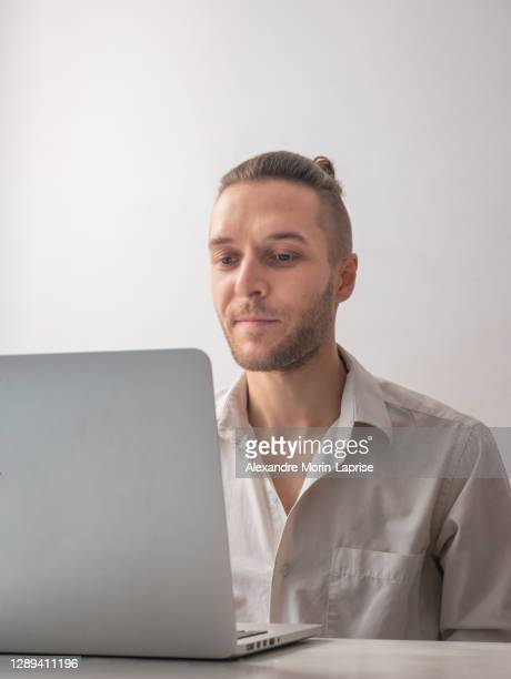 caucasian man smiling in front of the computer, talking on video call in quarantine for the coronavirus pandemic - 30 34 years stock pictures, royalty-free photos & images