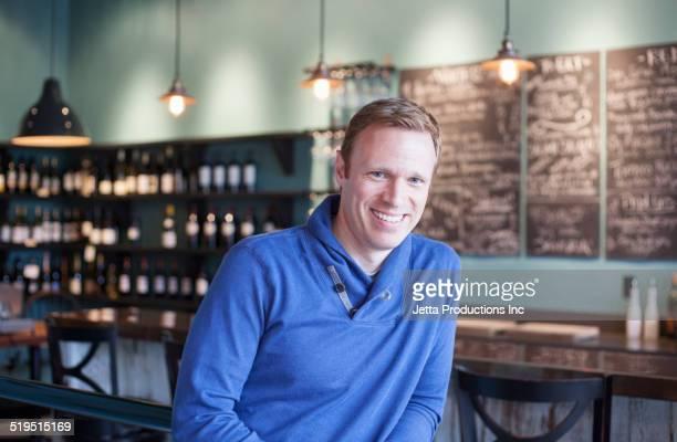 caucasian man smiling in wine bar - bainbridge island stock pictures, royalty-free photos & images
