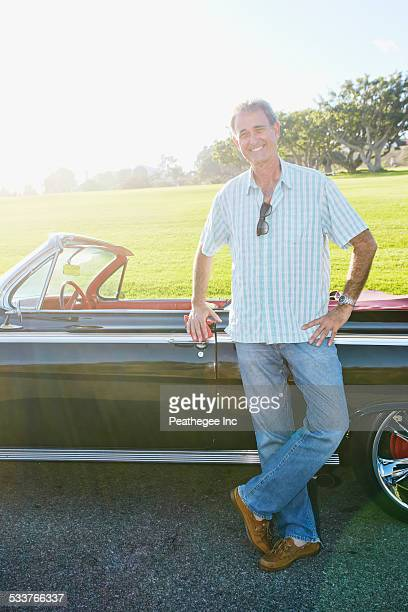 Caucasian man smiling near classic convertible