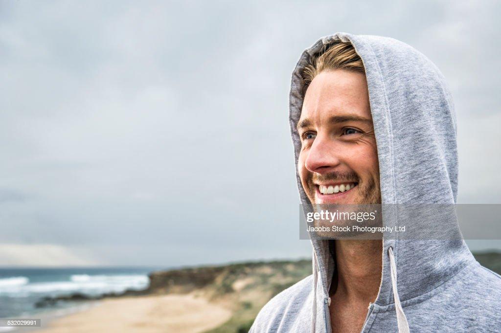 Caucasian man smiling on beach : Stock Photo