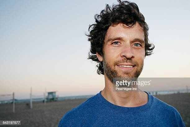 caucasian man smiling on beach - black hair stock pictures, royalty-free photos & images