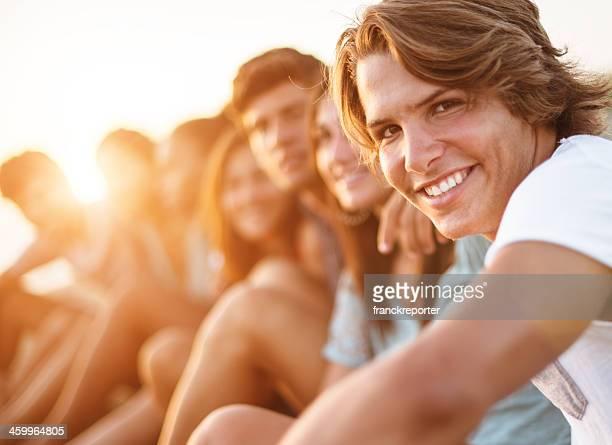 Caucasiano homem sorridente na praia com os seus amigos