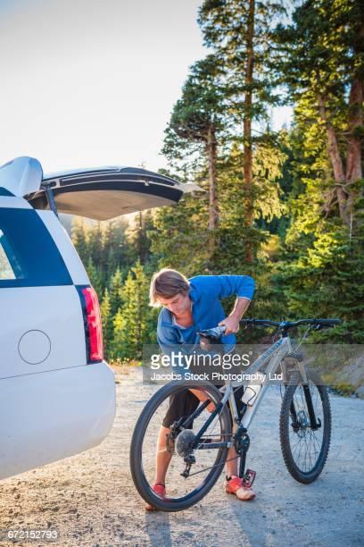 caucasian man spinning mountain bike wheel near car - 積荷を降ろす ストックフォトと画像