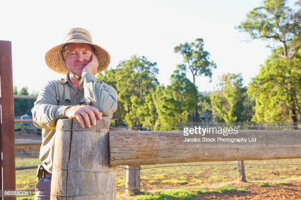Caucasian man standing at farm fence