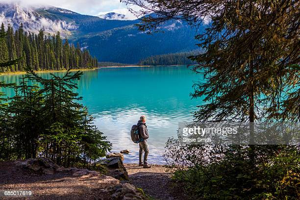 Caucasian man standing at mountain lake