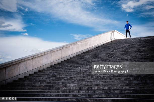 caucasian man standing at top of staircase - main sur la hanche photos et images de collection