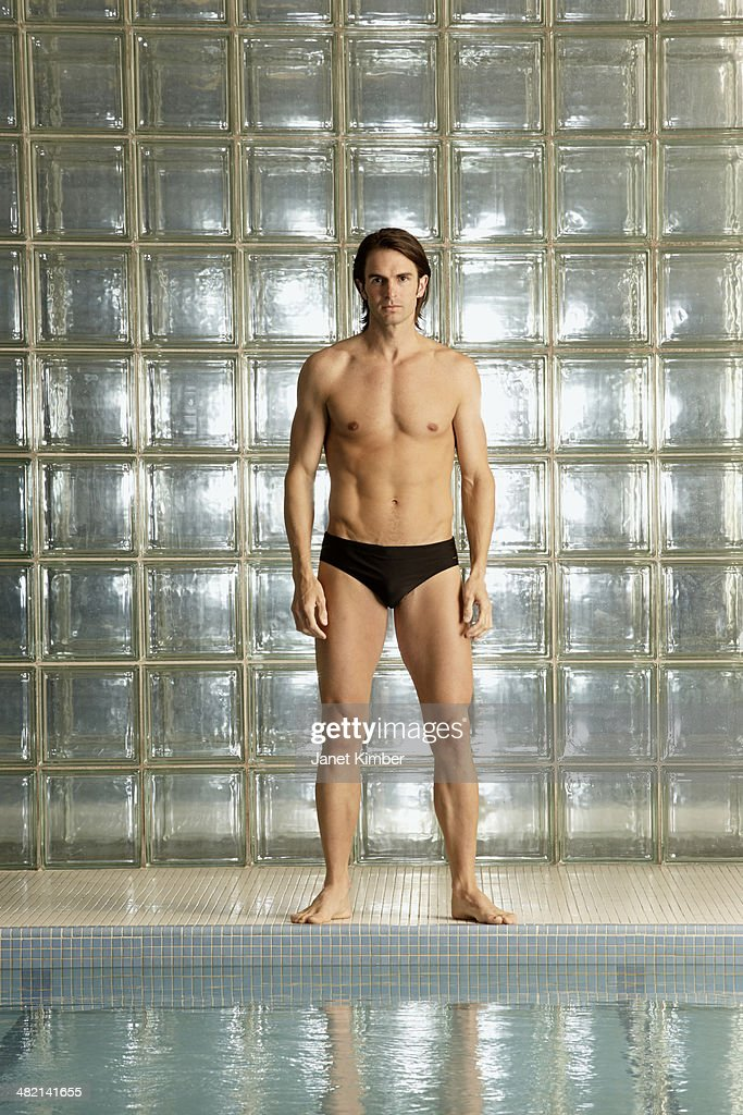 Caucasian man standing by pool : Stock Photo