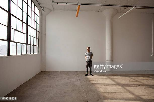 caucasian man standing in empty loft - hommes nus photos et images de collection