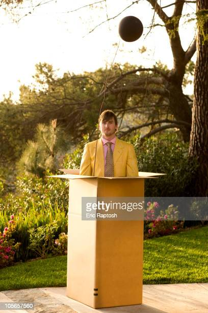 Caucasian man standing in large cardboard box outdoors