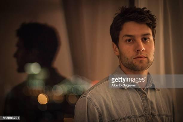 Caucasian man standing near window at night