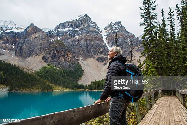 Caucasian man standing on boardwalk admiring mountain