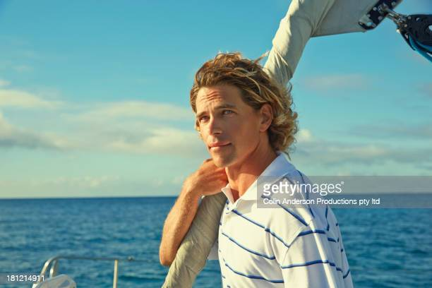 Caucasian man standing on sailboat