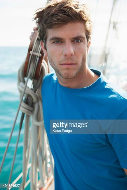 Caucasian man standing on sailboat