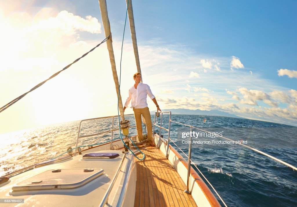 Caucasian man standing on yacht deck : Foto stock