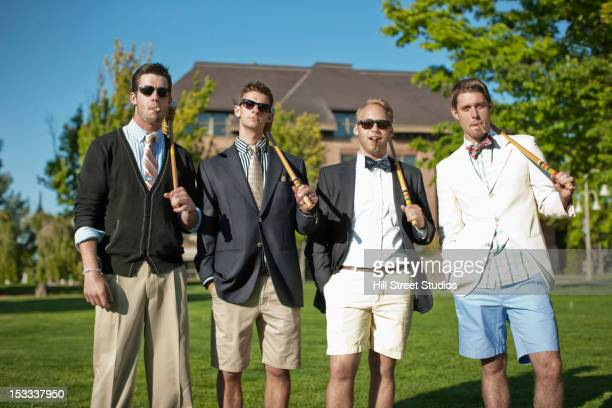 caucasian man standing together with croquet mallets - smart casual stock pictures, royalty-free photos & images