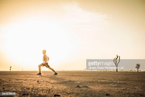 Caucasian man stretching in desert