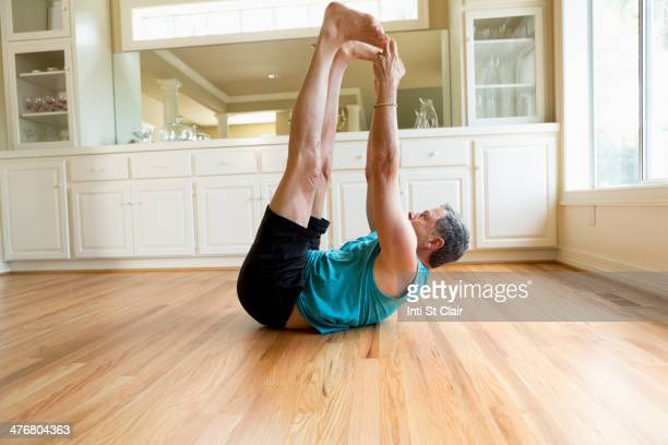 Caucasian man stretching in home
