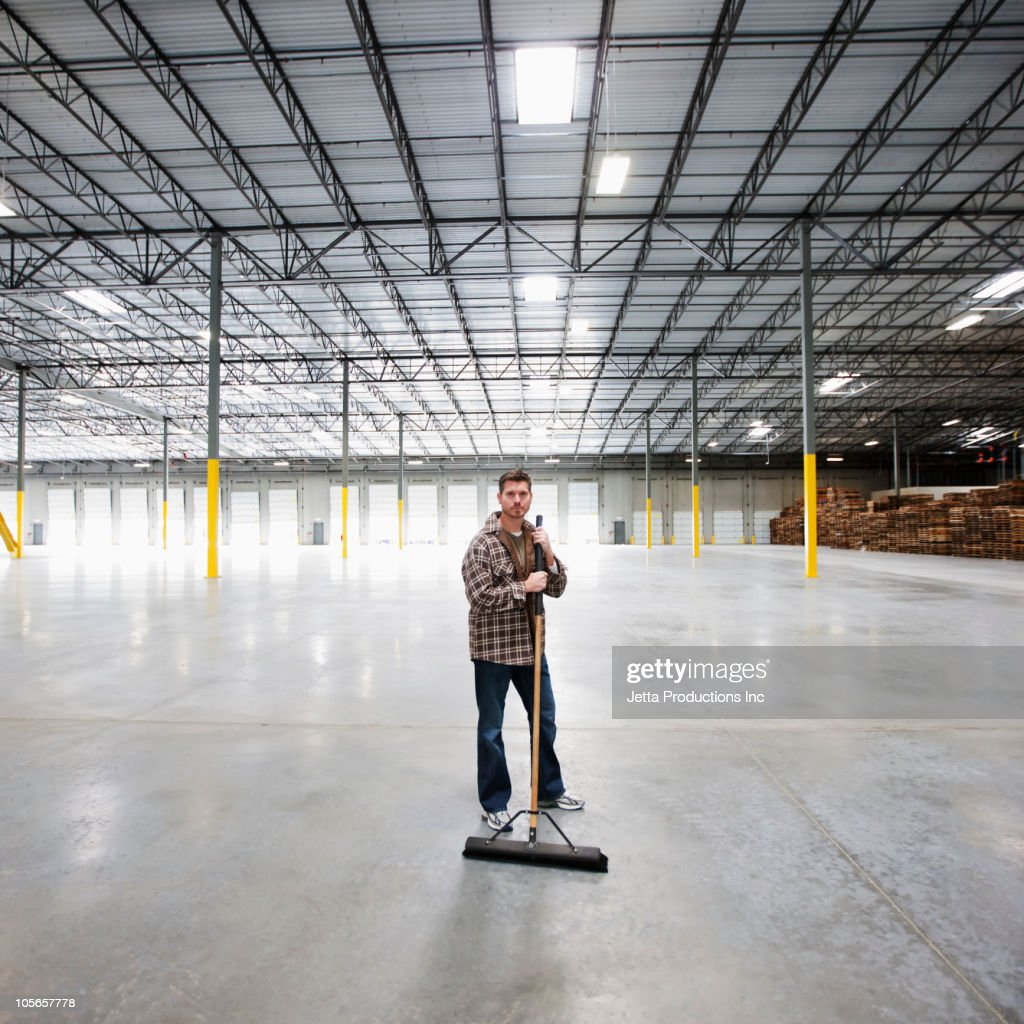 Caucasian man sweeping large, empty warehouse : Stock Photo