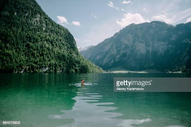 Caucasian man swimming in mountain lake