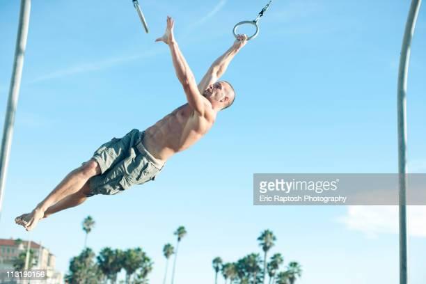 Caucasian man swinging on gymnastic rings