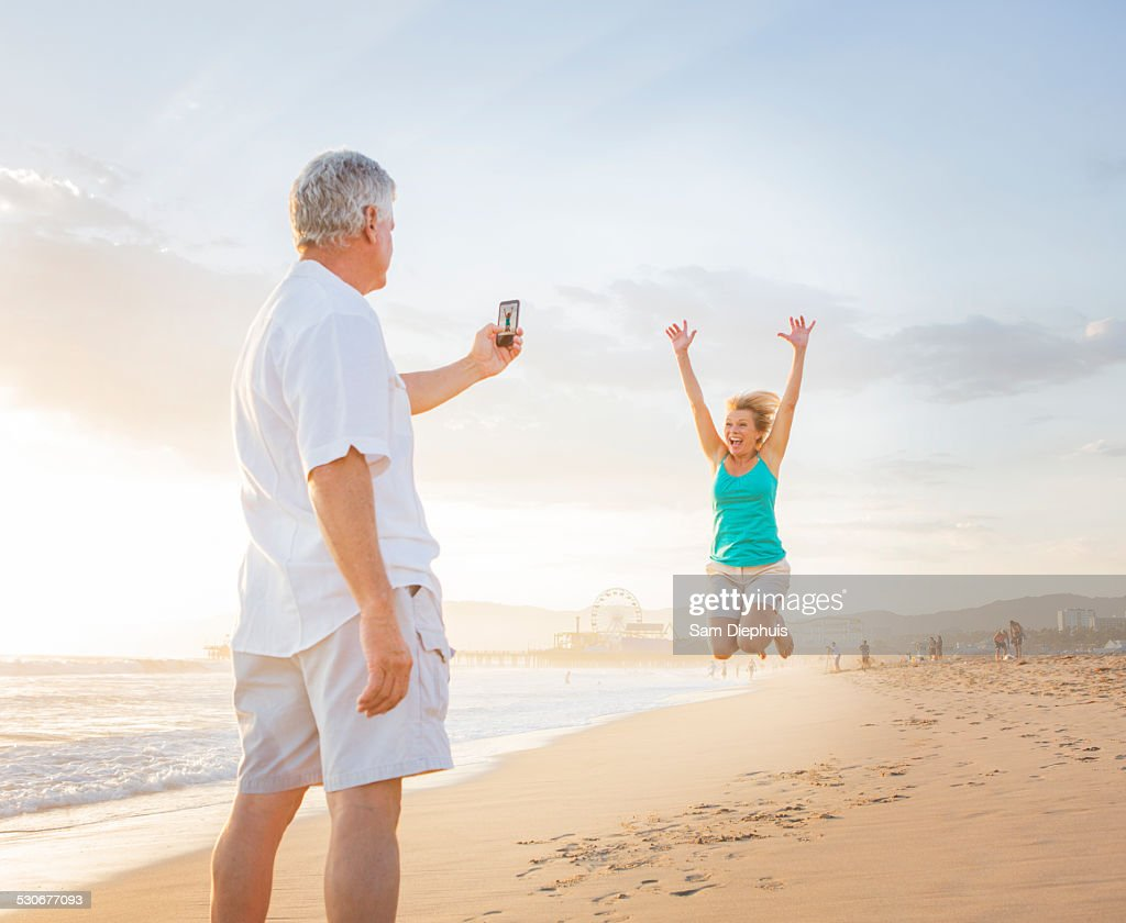 Caucasian man taking cell phone photograph of wife on beach : Stock Photo