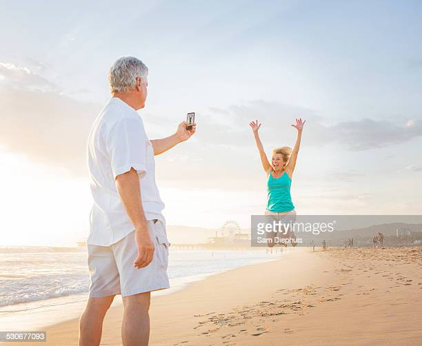 caucasian man taking cell phone photograph of wife on beach - hot women pics stock pictures, royalty-free photos & images