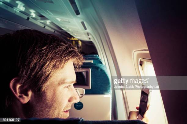 Caucasian man taking cell phone photograph out airplane window