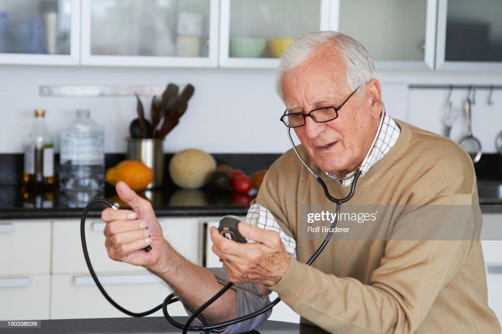 Uomo caucasico prendendo la Sua pressione sanguigna : Foto stock