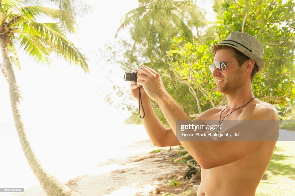 Caucasian man taking photograph on tropical beach : Foto stock