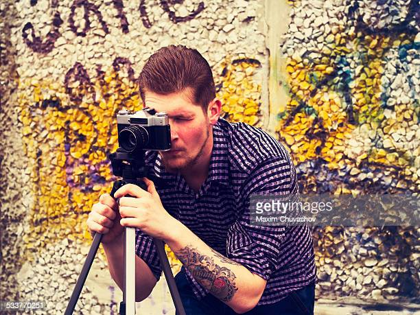 Caucasian man taking photograph outdoors