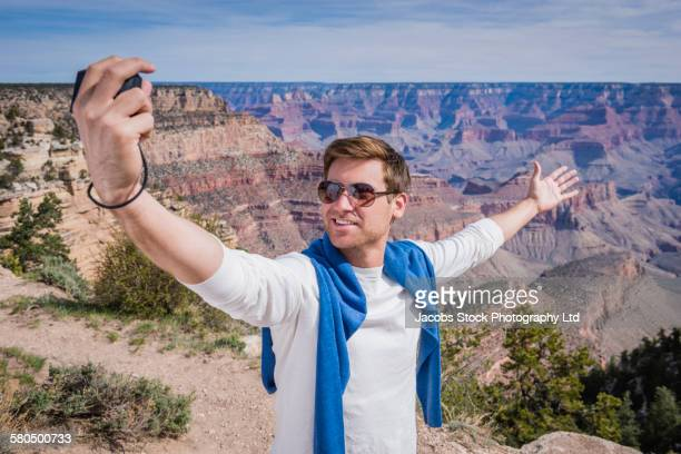 Caucasian man taking self-portrait in Grand Canyon, Arizona, United States
