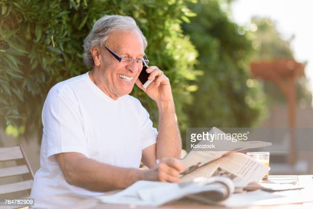 Caucasian man talking on cell phone and reading newspaper
