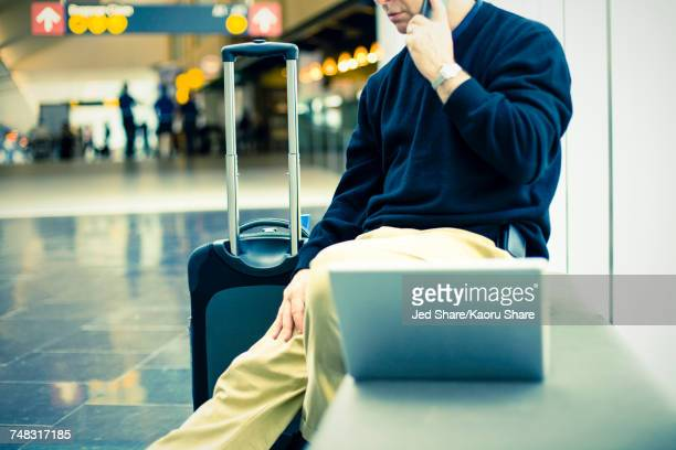 Caucasian man talking on cell phone at airport