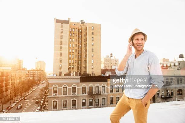 Caucasian man talking on cell phone on urban rooftop
