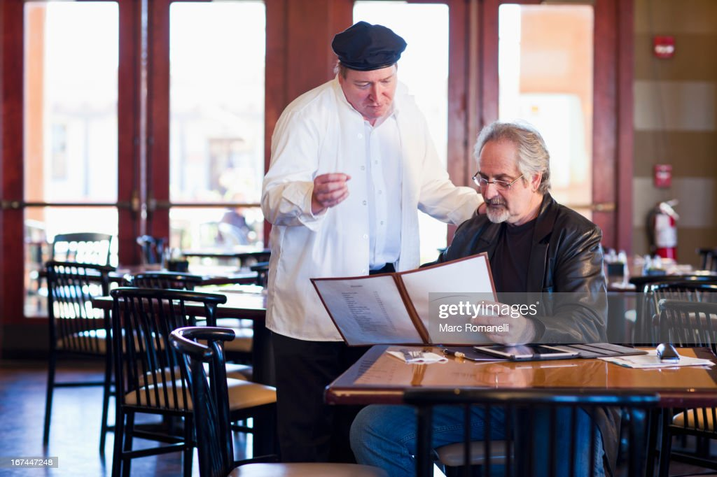 Caucasian man talking to chef in restaurant : Stock Photo