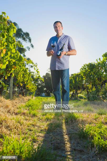 Caucasian man tasting wine in vineyard