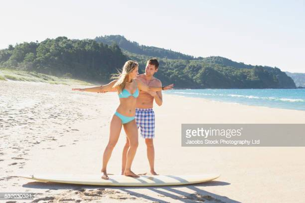 Caucasian man teaching girlfriend to surf on beach