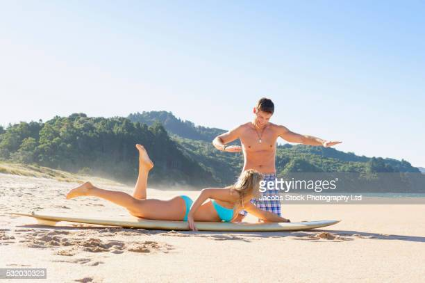 caucasian man teaching girlfriend to surf on beach - whangarei heads stock pictures, royalty-free photos & images