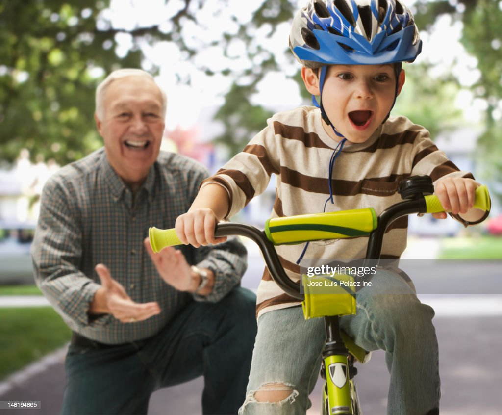 Caucasian man teaching grandson to ride a bicycle : Stock Photo