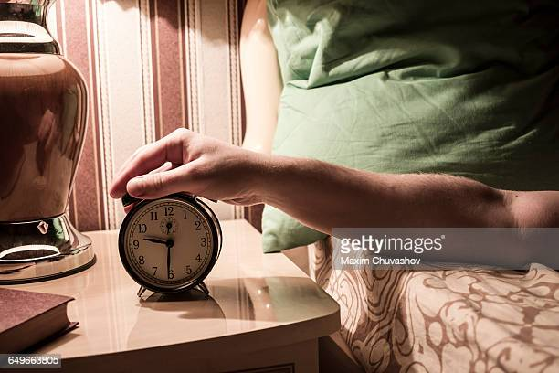 Caucasian man turning off alarm clock