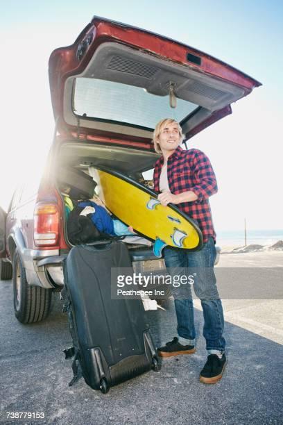 Caucasian man unloading surfboard from car hatch